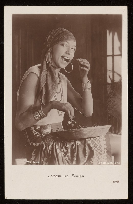 Sepia-toned photograph of Josephine Baker seated, eating fruit out of a large bowl, wearing a headscarf.