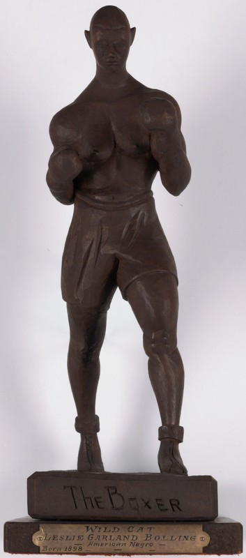 Front-view of a small wooden sculpture of a boxer in striking position.