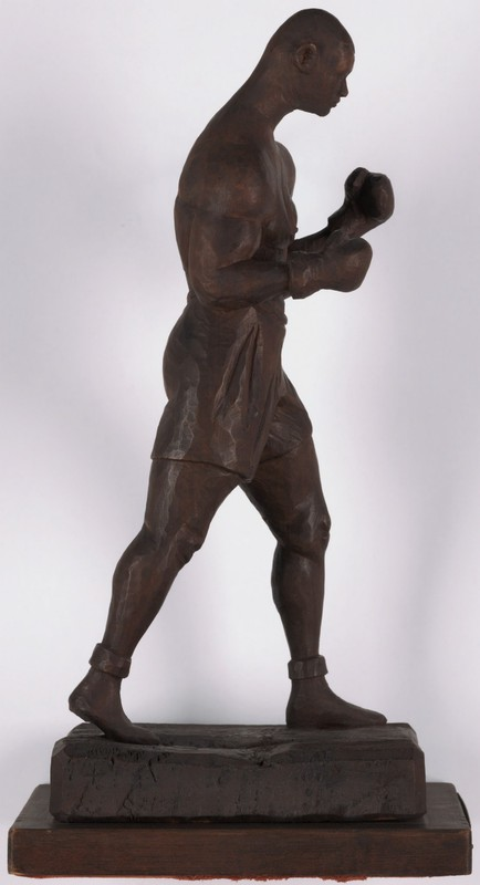 Profile-view of a small wooden boxer in striking position.