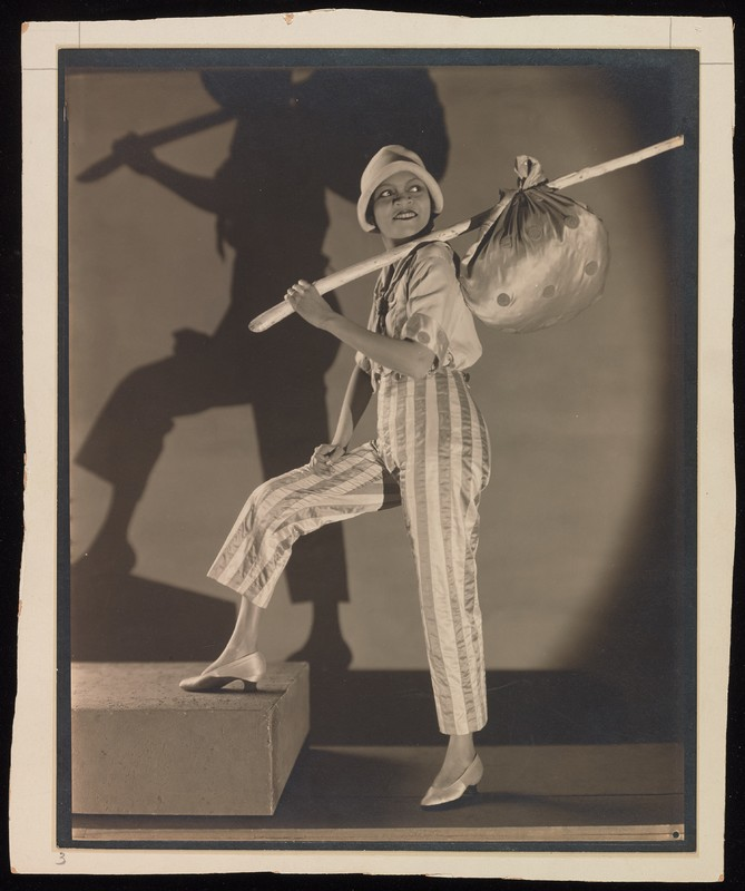 Portrait of Florence Mills in black and white, standing and holding a stick with a sack on the end.
