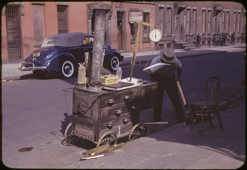 Photograph of a man wearing a hat with a street cart and scale.