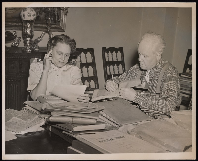 Black-and-white Photograph of Grace Nail Johnson and Carl Van Vechten sitting at a table covered in books and papers.