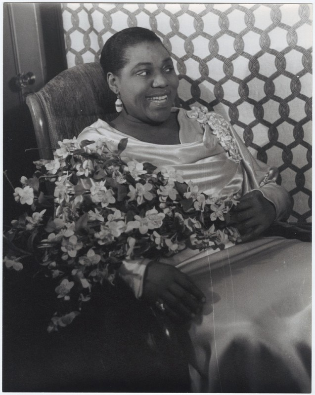 Black and white photograph of Bessie Smith, sitting with a bouquet of flowers and smiling.