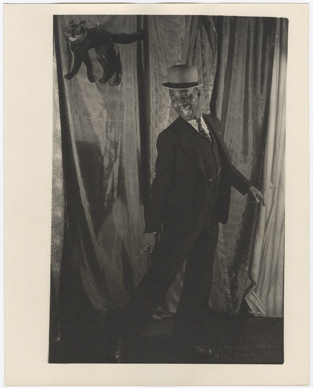 Standing portrait of Bill Robinson with a hat and cane