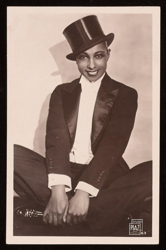 Black-and-white photograph of Josephine Baker wearing a tux, sitting cross-legged.