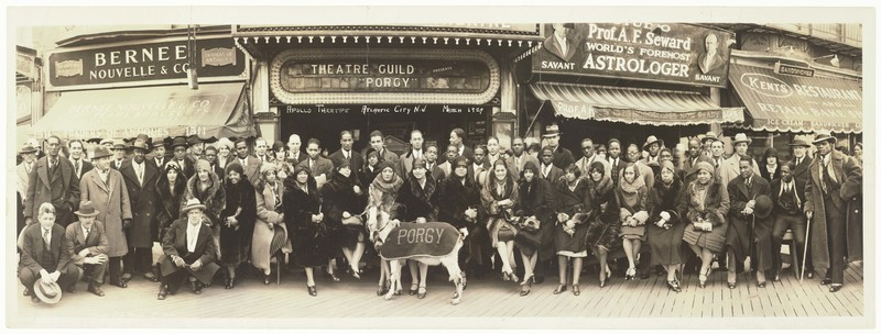 """Panoramic black-and-white photograph of the cast of Porgy, with a  goat in the front wearing a coat that says """"Porgy."""""""