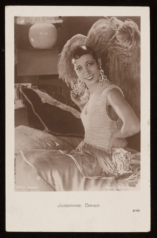 Sepia-toned photo of Josephine Baker seated, wearing extravagant beaded dress, a feathery headdress,  and big, dangling earrings.