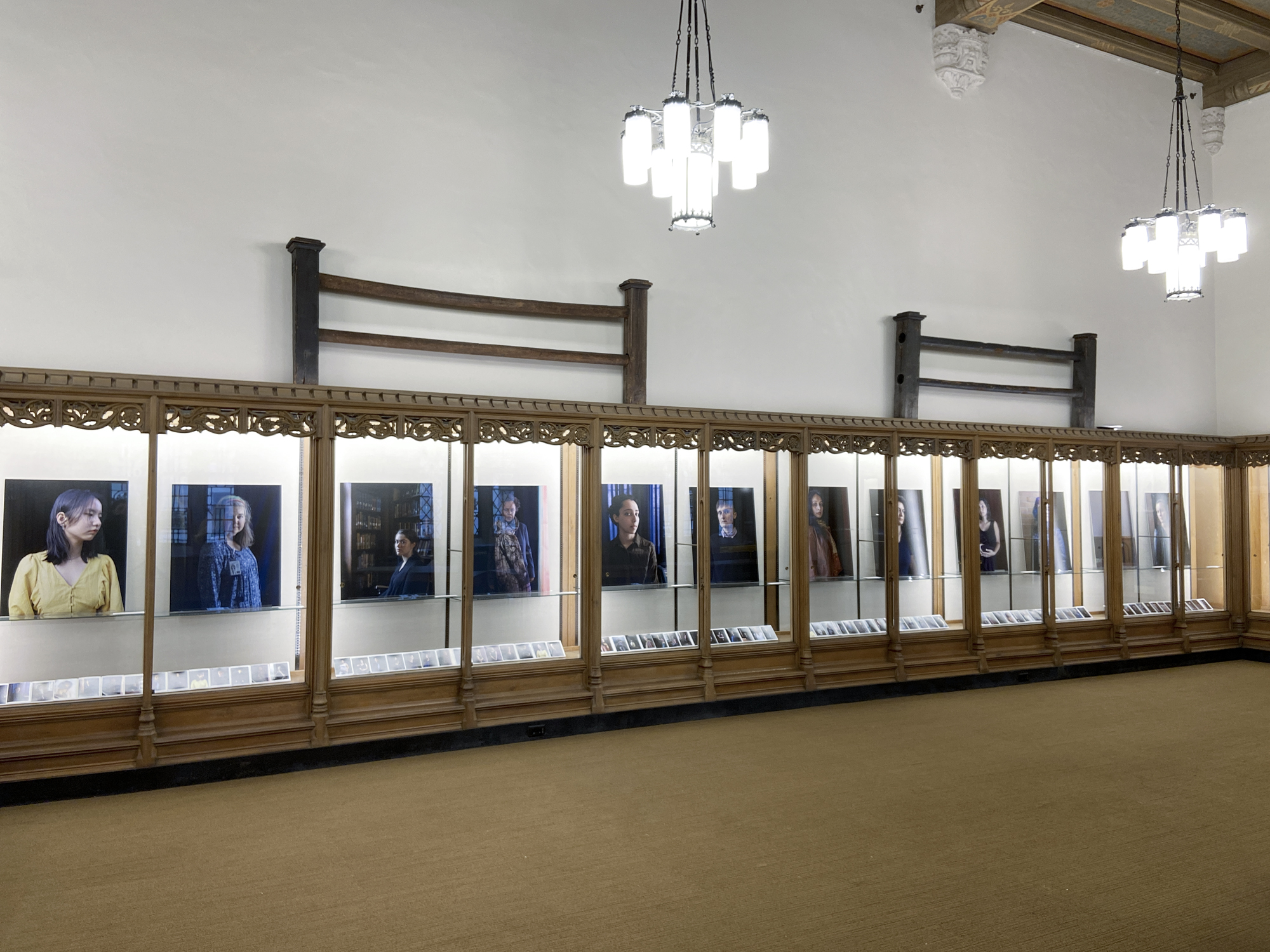 A installation shot of the 12 Portraits exhibit of a panoramic view of the wall of wooden glassed in cases showing all twelve of the photographic portraits on display in the space. Below the portraits, an array of small contact sheets are set out on the bottom shelf of the case in a neat row.
